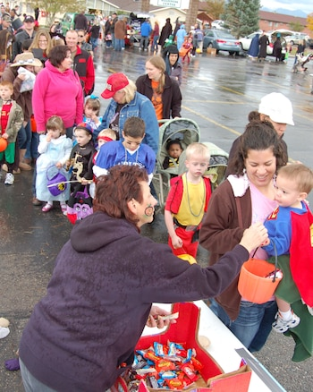 Ruth Schiele, wife of Chief Master Sgt. Steven Schiele, 151st Air Refueling Wing Chief's Council, passes out candy at the annual Utah National Guard Trunk or Treat event, held at Camp Williams, Utah, on Oct. 30, 2010. This year's event attracted hundreds of children along with their parents, despite cold rainy weather. (U.S. Air Force photo by Master Sgt. Gary Rihn)(RELEASED)