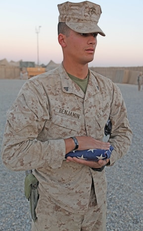 Cpl. Amos T. Benjamin, an infantry-man with 2nd Battalion, 9th Marine Regiment, stands at attention with a folded American Flag during evening colors at Marine Corps Forward Operating Base Camp Hansen, Helmand Province, Afghanistan, Nov. 8. Benjamin's brother, Master Sgt. Adam F. Benjamin, was killed in Helmand Province last year and has used the deployment to honor his brother's sacrifice.