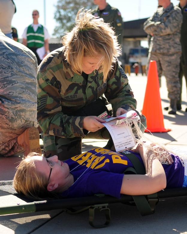 DAVIS-MONTHAN AIR FORCE BASE, Ariz. - Tech. Sgt. Nichole Helsley, from the 355th Aerospace Medicine Squadron, performs an initial medical assessment on a patient as part of a National Disaster Medical Systems Exercise on the Snowbird ramp here Nov. 4. Airmen from the 355th MDG and civilian medical personnel from various agencies in Tucson participated in the NDMSE, which is designed to test the ability of military and civilian medical groups to work together to receive casualties, provide triage, and transport patients to area hospitals in the event of a crisis. (U.S. Air Force photo/Airman 1st Class Jerilyn Quintanilla)