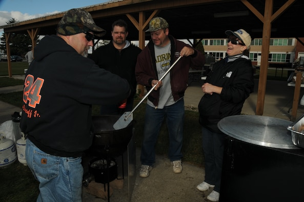 Members of the Ohio chapter of Barbecue for Our Troops huddle by one of five smokers used to feed hungry troops Oct 3, at the 180th Fighter Wing Pavillion. The picnic was provided by the group to celebrate the Excellent rating the base received in the Operational Readiness Inspection this summer and to salute our Hometown Heroes.