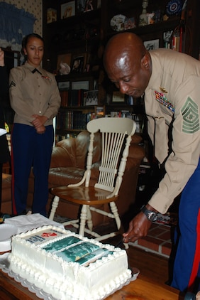 Sergeant Maj. Carlton W. Kent, the 16th Sergeant Major of the Marine Corps, cuts the birthday cake at a small birthday celebration Nov. 10, 2010 in the home of retired Sgt. Maj. Henry H. Black, the 7th SMMC, as the youngest Marine present, Cpl. Rocio Iribelopez, looks on.  Approximately 20 Marines and family members made the trip to Black's home in Fredericksburg, Va., to ensure he had a proper celebration of the Corps' 235th birthday.