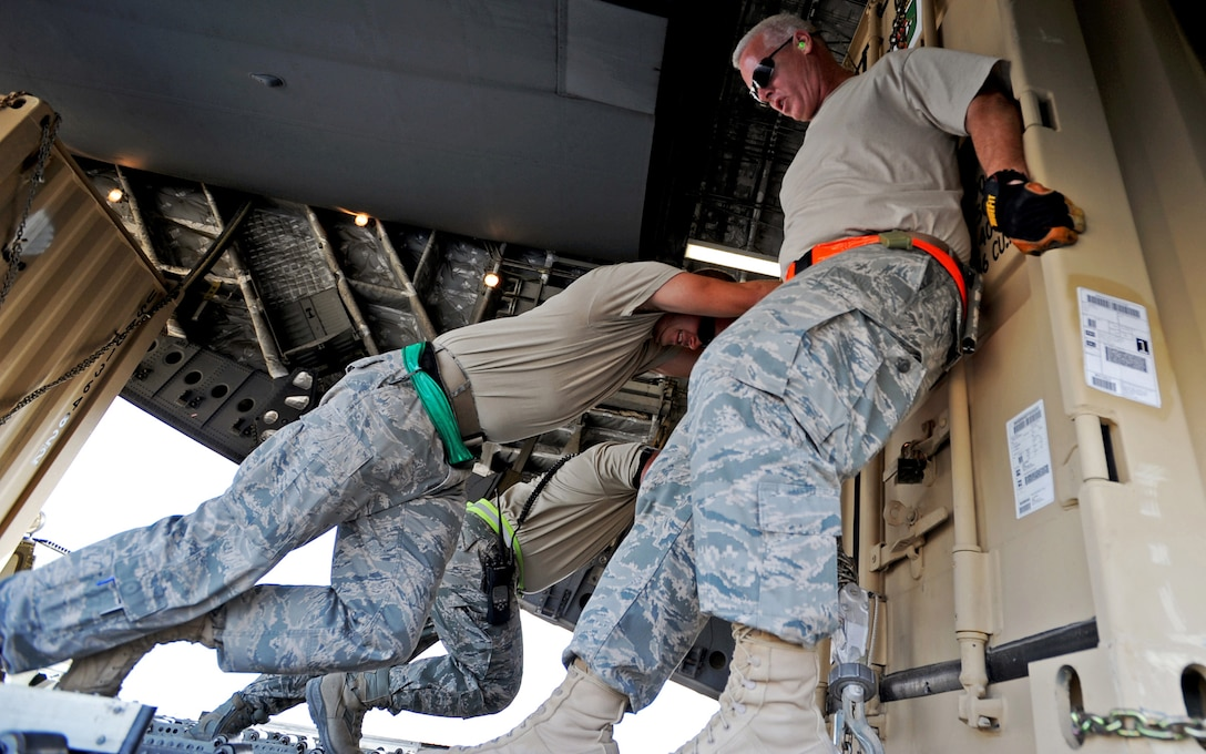 """SOUTHWEST ASIA - Airmen from the 386th Expeditionary Logistics Readiness Squadron Aerial Port use muscle power to push a pallet of cargo onto a C-17 Globemaster III at an undisclosed air base here Nov. 3, 2010. Known informally as """"Port Dogs,"""" Aerial port Airmen inspect and palletize all cargo before shipment, from food and water to ammunition and rolling stock. They also work closely with aircraft loadmasters to carefully position the cargo inside aircraft, loading it into planes with massive forklifts or special flat-bed trucks known as K-loaders. (U.S. Air Force photo by Senior Airman Laura Turner)"""