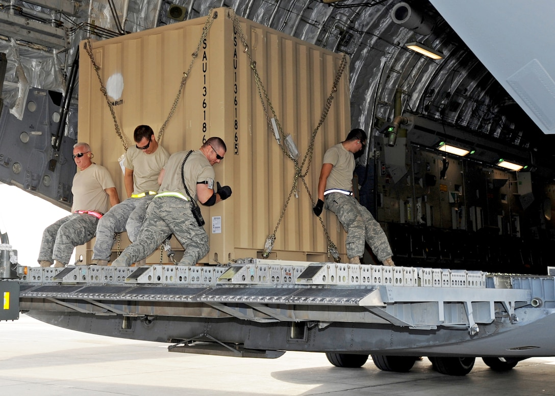 "SOUTHWEST ASIA - Airmen from the 386th Expeditionary Logistics Readiness Squadron Aerial Port move a pallet of cargo onto a C-17 Globemaster III at an undisclosed air base here Nov. 3, 2010. Known informally as ""Port Dogs,"" Aerial port Airmen inspect and palletize all cargo before shipment, from food and water to ammunition and rolling stock. They also work closely with aircraft loadmasters to carefully position the cargo inside aircraft, loading it into planes with massive forklifts or special flat-bed trucks known as K-loaders. (U.S. Air Force photo by Senior Airman Laura Turner)"
