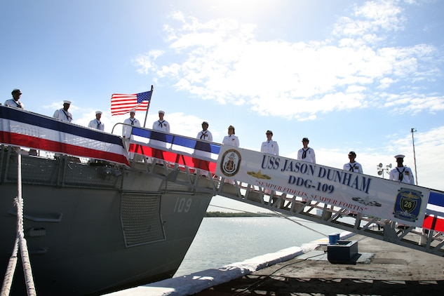 The crew of the Arleigh Burke class destroyer USS Jason Dunham mans the rails for the first time Nov. 13, 2010 at Port Everglades, Fla. The ship's commissioning ceremony paid homage to its namesake, Cpl. Jason Dunham, who selflessly sacrificed his life at age 22 in Iraq, April 14, 2004.