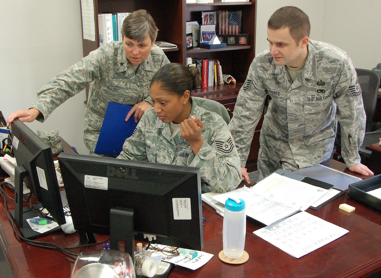 Brig Gen. Teresa Djuric, former Holm Center commander, Tech. Sgt. Renika Kenan, NCOIC, executive services, Holm Center, and Tech. Sgt. Damien Pierce, executive assistant, Holm Center, team up to solve an Officer Training School-related issue last month. (Air Force Photo/Airman 1st Class Christopher S. Stoltz)