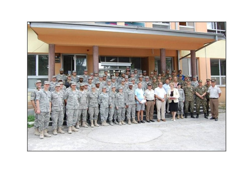 136th Civil Engineering Squadron, Texas Air National Guard, Bosnian Officials and friends pose in front of the school the unit help renovate along with (right to left) members of the Bosnian military, staff of the Office of Defense Cooperation, Vice-Principal, Mayor, General Puljic, and Principal. (Courtesy photo by 136 CES)