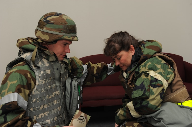 U.S. Air Force Chaplain (1st Lt.) Robert Stone consoles Master Sgt. Sherry Bishop, both from the 136th Airlift Wing, Texas Air National Guard, by praying with her in her time of spriritual distress during an operational readiness exercise at NAS Fort Worth, Carswell Field, Texas, Oct. 29, 2010. (U.S. Air Force photo by Tech. Sgt. Charles Hatton/released)