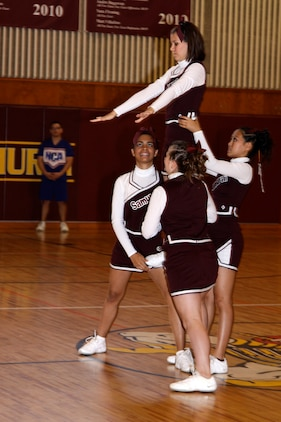 Matthew C. Perry High School Samurai cheerleaders Karly Chambers, Patricia Mojica, Lydia Pierce and Destynee Santiago prepare for a stunt as part of their team routine during the final competition of the National Cheerleading Association cheerleading clinic held at the Matthew C. Perry High School gymnasium here Nov. 12.