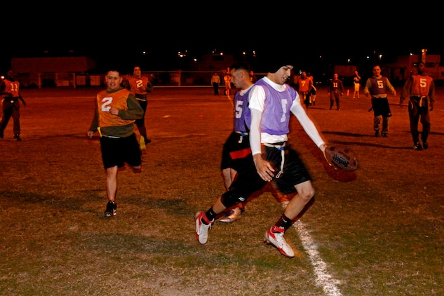 Paul Torres, quarterback for Da Freaks, holds the ball out for a touchdown after a ten-yard scramble during an Intramural Flag Football game at the Penny Lake football field here Monday. Da Freaks blew the Wreckin' Crew out of the water with a 37-19 beat down before the game was called due to the mercy rule.