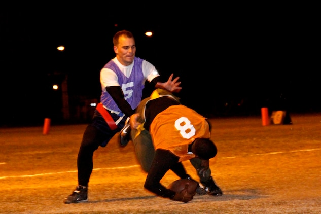 Randy Bascom, quarterback for Wreckin' Crew, loses his footing as he scrambles for a first down during a losing effort against Da Freaks at the Penny Lake football field here Monday. Da Freaks routed the Wreckin' Crew 37-19 utilizing the mercy rule.