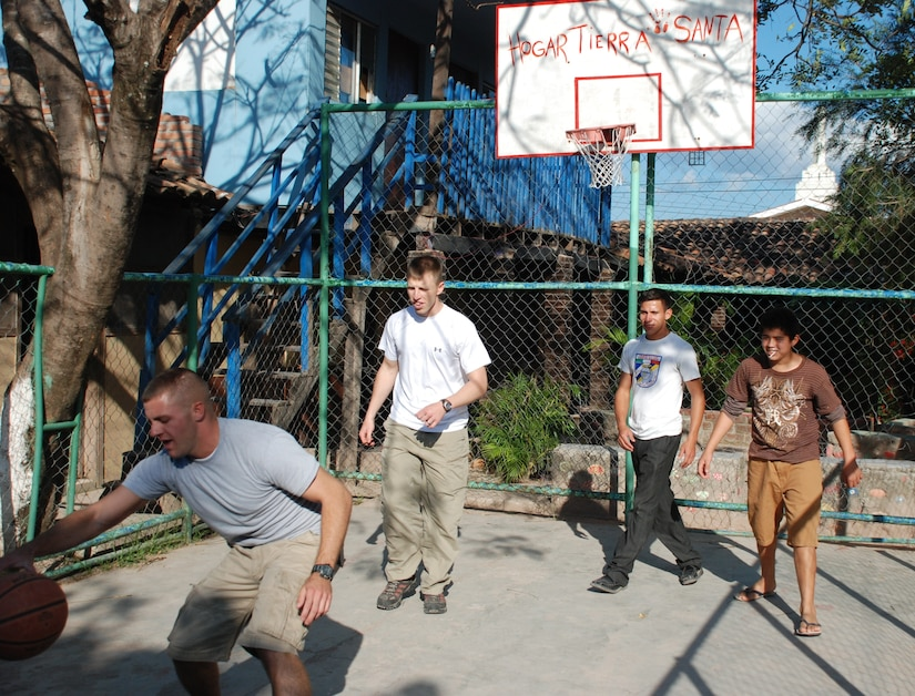 SOTO CANO AIR BASE, Honduras - U.S. Air Force 2Lt. Nicholas Kerner (left) and U.S. Army 1Lt Aaron Anderson (second from left), play a game of basketball with a couple young adults at the Hogar Tierra Santa Orphanage, Sunday, 14 Nov 2010.  20 members of the Joint Task Force-Bravo team visited the children to serve them dinner, bring clothing and participate in games and laughter.  The 0rphanage is just one of several that are sponsored by members of JTF-B. (U.S. Air Force photo/Capt. John T. Stamm)