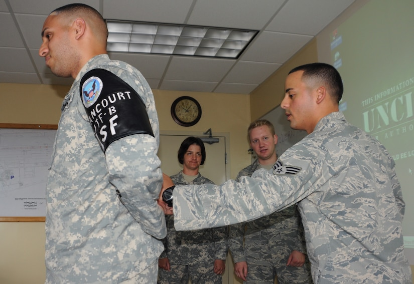 SOTO CANO AIR BASE, Honduras --  Senior Airman Jaime Perez, right, of the Joint Security Forces Squadron, shows augmentee trainees how to maintain control over a suspect, played by Spc. Dionny Betancourt, of the JSF, before handcuffing him here recently. (U.S. Air Force photo/Tech. Sgt. Benjamin Rojek)