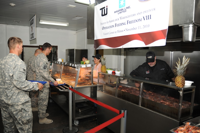 TRANSIT CENTER AT MANAS, Kyrgyzstan - Deployed military troops receive meals prepared by Outback Steakhouse Incorporated (OSI) employees during an Armed Forces Entertainment tour to the Transit Center at Manas Nov. 11.  OSI owns Outback Steakhouse, Carrabba's Italian Grill, Bonefish Grill, Fleming's Prime Steakhouse and Wine Bar and Roy's Hawaiian Fusion Cuisine.  Employees volunteered to visit with the troops and prepared 4,400 meals here in celebration of Veterans Day.   (U.S. Air Force photo/Staff Sgt. Nathan Bevier)
