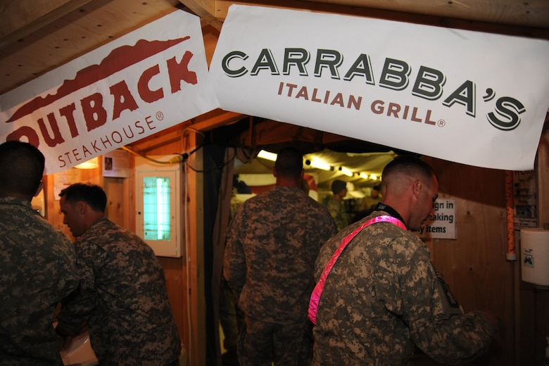 TRANSIT CENTER AT MANAS, Kyrgyzstan - Deployed military troops receive meals prepared by Outback Steakhouse Incorporated (OSI) employees during an Armed Forces Entertainment tour to the Transit Center at Manas Nov. 11.  OSI owns Outback Steakhouse, Carrabba's Italian Grill, Bonefish Grill, Fleming's Prime Steakhouse and Wine Bar and Roy's Hawaiian Fusion Cuisine.  Employees volunteered to visit with the troops and prepared 4,400 meals here in celebration of Veterans Day.   (U.S. Air Force photo/Staff Sgt. Michael Schocker)