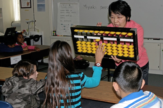 Miyuki Inoashi, a master teacher of soroban, makes sure students understand how to use the tool by having them demonstrate on her much larger version during a training session at Matthew C. Perry Elementary School here Nov. 16. Soroban is an advanced mathematical ability supporting one's mental calculation aptitude and facilitates a better understanding of the number concept, base ten systems and place value.