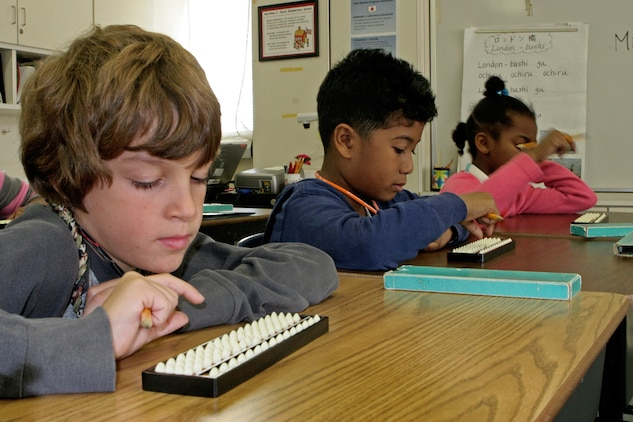 Students practice using their sorobans during a training session from Miyuki Inoashi, a master teacher of soroban, at Matthew C. Perry Elementary School here Nov. 16. The tool is used to calculate various types of mathematical equations.
