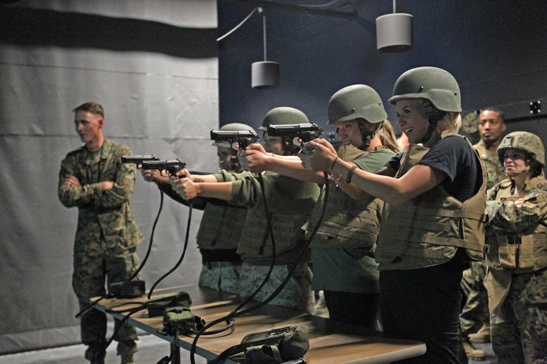 Wives with 2nd Battalion, 7th Marine Regiment's Jane Wayne Day fire off rounds at the Indoor Simulated Marksmanship Trainer during their trip there Wednesday. The day is meant to build camaraderie amongst spouses within the battalion. ::r::::n::