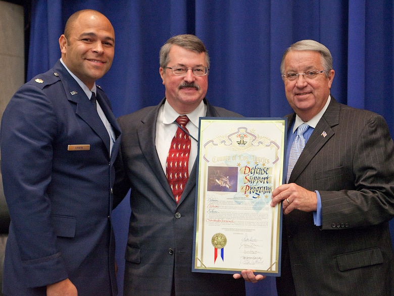 Los Angeles County Supervisor Don Knabe presents a proclamation to Maj. Johnny Erwin, Infrared Space Systems Directorate, and John Kravec, Northrop Grumman DSP program operations manager, at the county supervisors meeting, Nov. 9. The program celebrates its 40th Anniversary this year. (Photo courtesy of Northrop Grumman)