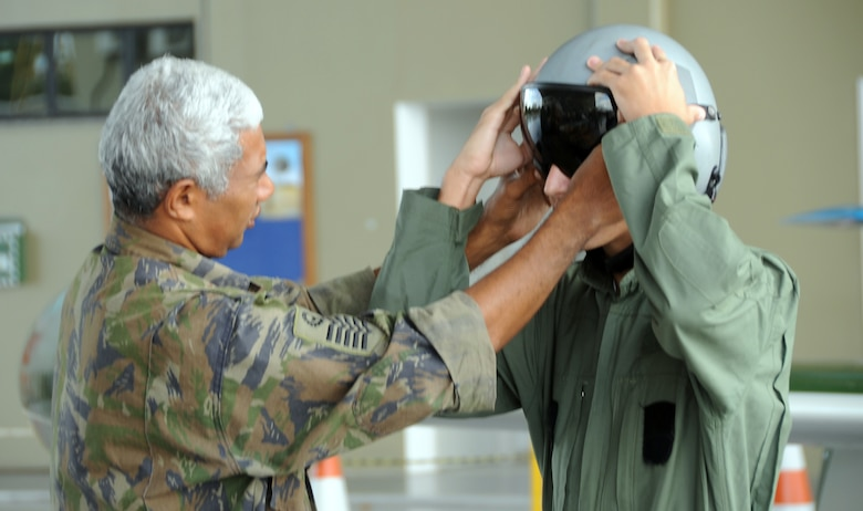 A local youth is fitted in a helmet during an open house at Natal Air Base, Brazil in conjunction with CRUZEX V. CRUZEX, or Cruzeiro Do Sul (Southern Cross), is a multi-national combined exercise involving the Air Forces of Argentina, Brazil, Chile, France and Uruguay, and observers from numerous other countries with more than 82 aircraft and almost 3,000 Airmen involved. (U.S. Air Force photo/Staff Sgt. Michael Matkin)