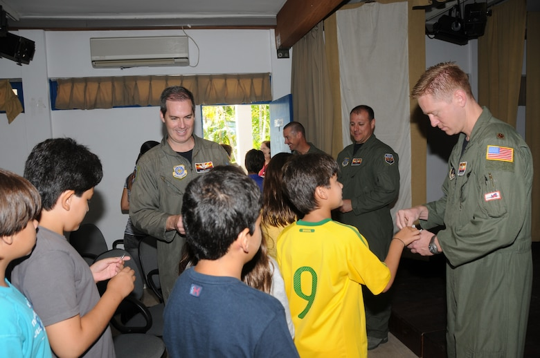 Members of the 161st Air Refueling Wing, Phoenix, Ariz., hand out coins to students from the American School of Recife on November 17, 2010, in Recife, Brazil. The 161st ARW is participating in CRUZEX V, or Cruzeiro Do Sul (Southern Cross).  CRUZEX  is a multi-national combined exercise involving the Air Forces of Argentina, Brazil, Chile, France and Uruguay, and observers from numerous other countries with more than 82 aircraft and almost 3,000 Airmen involved.    U.S. Air Force Photo by Master Sgt. Kelly Deitloff