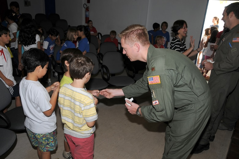 Major Steve Hutchinson of the 161st Air Refueling Wing, Phoenix, Ariz.,hands out coins to students from the American School of Recife on November 17, 2010, in Recife, Brazil. The 161st ARW is participating in CRUZEX V, or Cruzeiro Do Sul (Southern Cross).  CRUZEX  is a multi-national combined exercise involving the Air Forces of Argentina, Brazil, Chile, France and Uruguay, and observers from numerous other countries with more than 82 aircraft and almost 3,000 Airmen involved.    U.S. Air Force Photo by Master Sgt. Kelly Deitloff