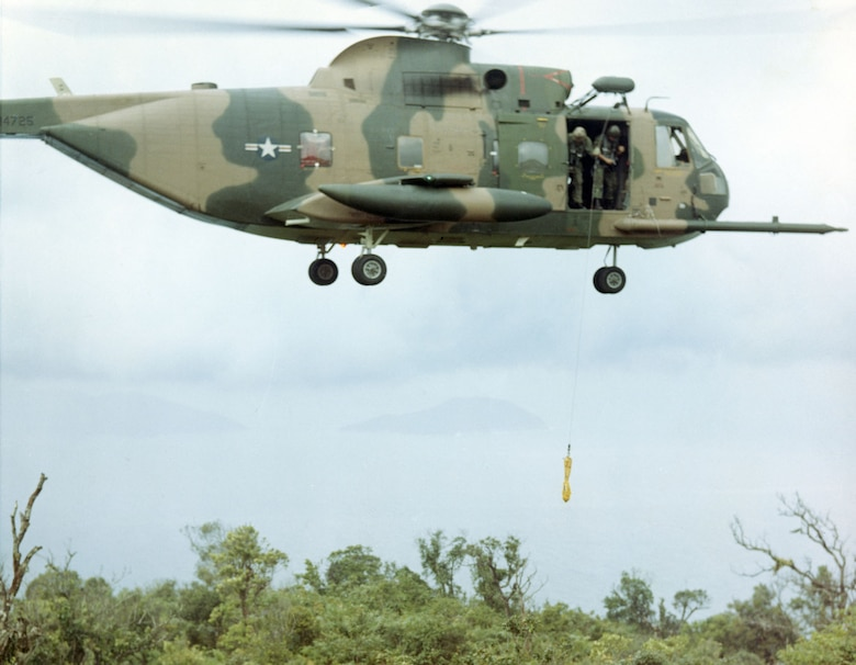 Equipped with a powerful external winch, the Jolly Green Giants could extract a downed pilot without landing. Here, an aircrew practices lowering a jungle penetrator. (U.S. Air Force photo)