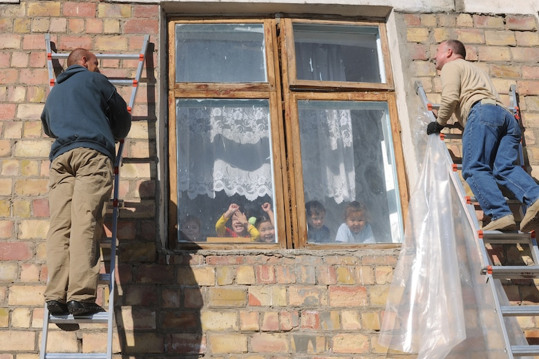 VASILIEVSKOE VILLAGE, Kyrgyzstan -  Staff Sgt. Thomas Love (left), 376th Expeditionary Civil Engineer Squadron humanitarian assistance, and Tech Sgt. Ron Warlick, 376th Expeditionary Communications Squadron, staple plastic over 20-year-old windows at Vasilievskoe Kindergarten as children look out the window Nov. 17.  The plastic will create a vapor barrier allowing most of the warm air to stay in the facility during Winter.  Over $10,000 have been spent on renovations for the school to include new windows and doors.  (U.S. Air Force photo/Staff Sgt. Nathan Bevier)