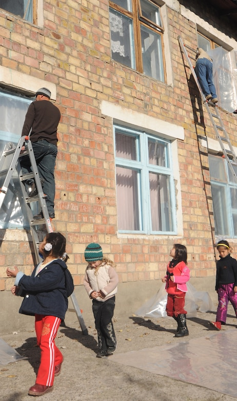 VASILIEVSKOE VILLAGE, Kyrgyzstan -  Staff Sgt. James Procaccini (left), 376th Expeditionary Civil Engineer Squadron humanitarian assistance, and Tech Sgt. Ron Warlick, 376th Expeditionary Communications Squadron, staple plastic over 20-year-old windows at Vasilievskoe Kindergarten as children return to class from a break Nov. 17.  The plastic will create a vapor barrier allowing most of the warm air to stay in the facility during Winter.  Over $10,000 have been spent on renovations for the school to include new windows and doors.  (U.S. Air Force photo/Staff Sgt. Nathan Bevier)