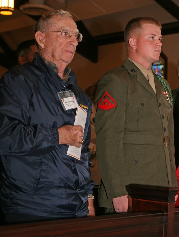 Lance Cpl. Justin M. Williams, a mortar man with 3rd Battalion, 6th Marine Regiment, 2nd Marine Division, stands at attention as Henry C. Norman, a veteran of the historic Battle of Tarawa during World War II, holds his hand over his heart during the Posting of the Colors. Tarawa veterans visited Camp Lejeune November 19 for the 67th anniversary of the Battle of Tarawa