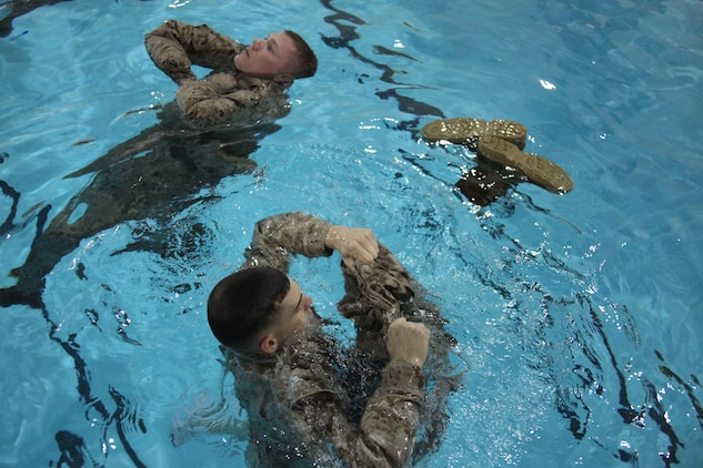 Effective now, the Marine Corps has implemented a new qualification system for combat water survival. The new system enhances safety, increases effectiveness and simplifies qualification requirements. Treading water is one portion of the Marine Combat Water Survival program that remains testable. One Marine preparing to use his utility trousers as a personal floatation device.