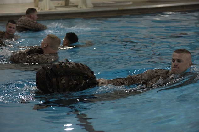 Gunnery Sgt. Michael Eason, an administration chief with Officer Candidate School, Marine Corps Base Quantico, Va., with assault pack in tow, swims to the opposite side of the pool during a demonstration for the new Marine Combat Water Survival Training, Nov. 19, 2010. One portion of the demo had the Marines use their assault pack as a floatation device.