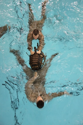 Two Marines swim to safety during a drowning victim recovery exercise at Ramer Hall, Marine Corps Base Quantico, Va., Nov. 19, 2010. The new Marine Combat Water Survival program also focuses on using gear to help Marines in water-borne situations.