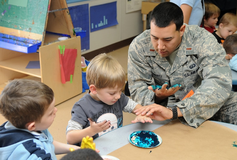"""Buckley Air Force Base, Colo.- 2nd Lt. Jared Rutkovitz goes """"blue"""" finger painting with some of the children at the Child Development Center honoring Native American Heritage month where volunteers from the Team Buckley spent the afternoon finger painting and making rain sticks. ( U.S. Air Force Photo by Airman First Class Marcy Glass )"""