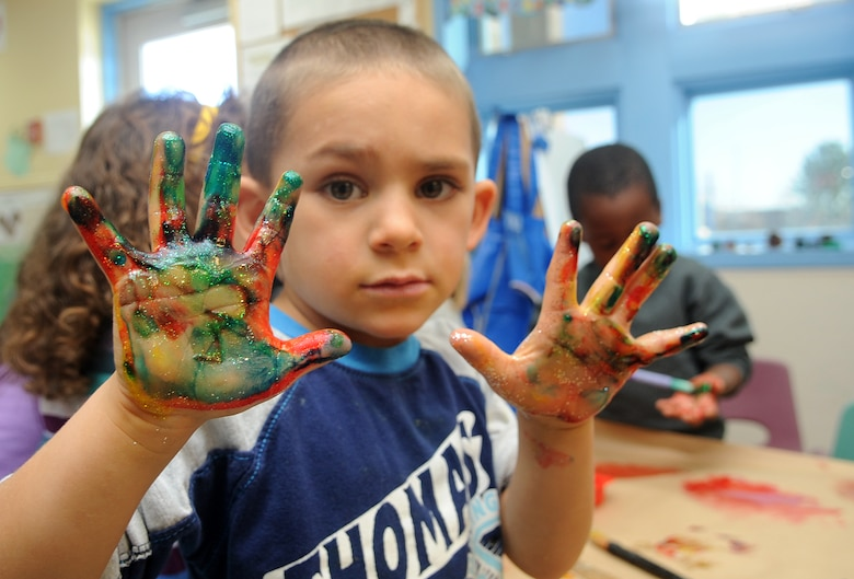 Buckley Air Force Base, Colo.- Daniel Rangel shows off his messy hands  at the Child Development Center where volunteers from the Team Buckley spent the afternoon finger painting and making rain sticks honoring Native American Heritage month. ( U.S. Air Force Photo by Airman First Class Marcy Glass )