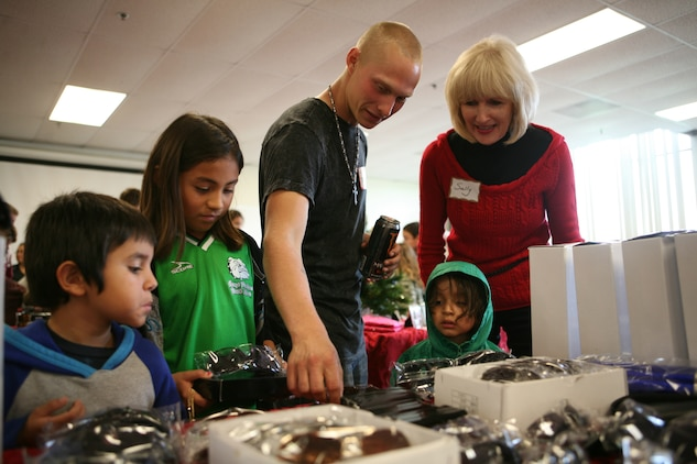 Lance Cpl. Justin L. Chase, a metal worker with 1st Light Armored Reconnaissance Battalion, and Sally L. McCoy, a Children Giving Gifts volunteer from Orange County, Calif., show Caleb, Naomi and Lucas Mata gifts items at Children Giving Gifts in San Mateo, Nov. 20. Children Giving Gifts, a non-profit organization, came to Camp Pendleton and allowed children to select gifts for their parents.