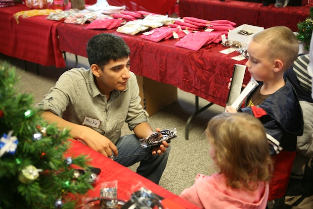 Petty Officer 3rd Class Micky A. Montoya, a corpsman with Headquarters and Service Company, 2nd Battalion, 5th Marine Regiment, talks to Sophia and Nathan Gaff about the gifts they selected for their parents at Children Giving Gifts in San Mateo, Nov. 20.  Nathan and Sophia are the children of Staff Sgt. Michael Gaff, and were two of more than a thousand kids participating in the first Children Giving Gifts hosted at Camp Pendleton.