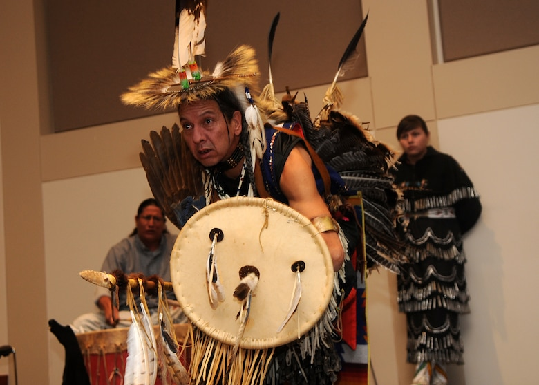 """Buckley Air Force Base, Colo.-  A dancer from the Denver Indian Center dances to the """"Sneak Up Song""""  performed  by the drummers depicting the tribe working together in tactical ways to sneak up on their enemies. ( U.S. Air Force Photo by Airman 1st Class Marcy Glass )"""