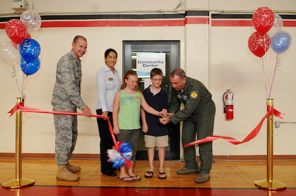 Brig. Gen. John Doucette, 36th Wing commander, Col. Alan Weider, 36th Mission Support Group commander, Ms. Michele Jacobs, 36th Force Support Squadron, Hotspot/Community  Activates director, Madison and Asher Guinzy cut the ribbon signifying the Grand Opening of the Community Center here, Nov. 19. (U.S. Air Force photo/Senior Airman Nichelle Anderson)
