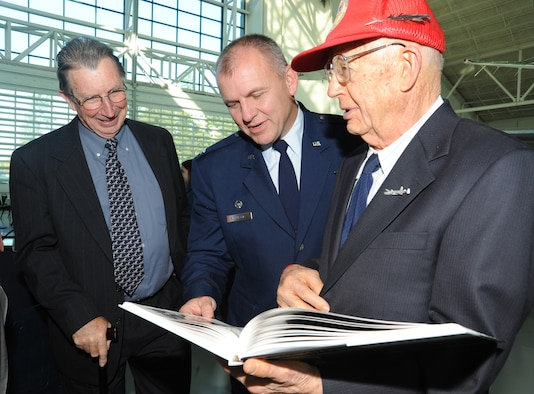"""Fred Hill shows off his book, """"Darkroom Soldier"""" to Oregon Air National Guard retired Major Gen. David E.B. Ward and 142nd Fighter Wing Commander Michael Bieniewicz after the Hall of Honor induction ceremony held at the Evergreen Aviation and Space museum in McMinnville, Ore., on October 17, 2010. Hill was one of the first members of the 123rd Observation Squardon, which was the first group inducted to the Hall of Honor. (U.S. Photograph by Staff Sgt. John Hughel, 142nd Fighter Wing Public Affairs Department)"""
