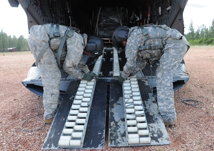 FUERZA MOROCON, Honduras --  Cpl. Brian Godfreaux, left, and Staff Sgt. Jeremy Dudley, both crew chiefs with the 1-228th Aviation Regiment, prepare the ramp of a CH-47 Chinook helicopter here Nov. 23. The 1-228th flew 44 rechargeable batteries to this remote base to ensure the Honduran Infantry Battalion has power during the night. (U.S. Air Force photo/Tech. Sgt. Benjamin Rojek)