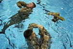 U.S. Marines tread water and one prepares to use his trousers as a flotation device during a demonstration of the new Marine combat water survival program on Marine Corps Base Quantico, Va., Nov. 19, 2010.