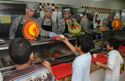 SOTO CANO AIR BASE, Honduras --  Working as a team, Command Sgt. Maj. Alvin Thomas, Lt. Col. James Kanicki and Command Sgt. Maj. Lucio DeAnda serve up a plat of Thanksgiving food to some family members here Nov. 25. Base leaders and other volunteers took turns serving holiday fair to Team Bravo during the lunch meal. (U.S. Air Force photo/Tech. Sgt. Benjamin Rojek)