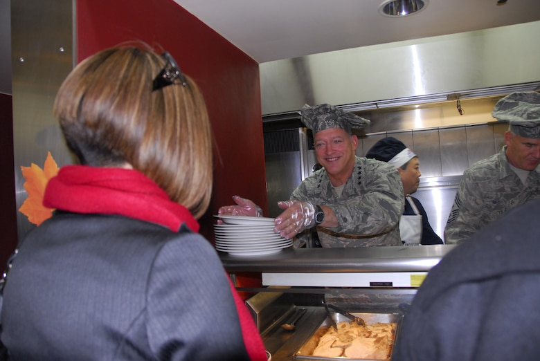Gen. Gary North, Pacific Air Forces commander, grabs a plate to serve turkey during a Thanksgiving meal Nov. 25 at the Gingko Tree dining facility, Osan Air Base, Republic of Korea. (U.S. Air Force photo/Staff Sgt. Eunique Stevens)