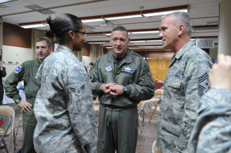 Gen. Gary North, Pacific Air Forces commander, center, and Chief Master Sergeant Sgt. Brooke McLean, PACAF command chief, right, talk with Airmen before a Thanksgiving meal Nov. 25 at the Gingko Tree dining facility, Osan Air Base, Republic of Korea. (U.S. Air Force photo/Staff Sgt. Eunique Stevens)
