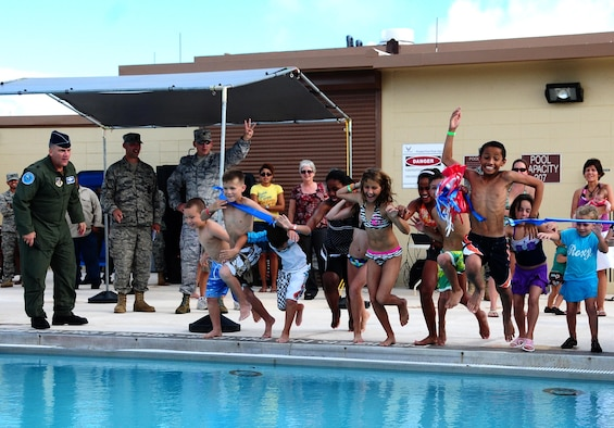 Brig. Gen. John Doucette, 36th Wing commander, looks on as Team Andersen children jump into the Andersen Air Force Base pool at the grand re-opening here Nov. 24. The pool reopened after undergoing more than a year of substantial renovations. (U.S. Air Force photo/Airman 1st Class Jeffrey Schultze)