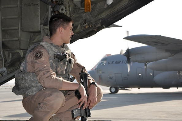 Senior Airman Jordan Gunterman crouches on the ramp of a Kentucky Air National Guard C-130 Hercules at Bagram Airfield, Afghanistan. Airman Gunterman is a 379th Air Expeditionary Wing fly-away security team leader. (U.S. Air Force photo/Capt. Erick Saks)