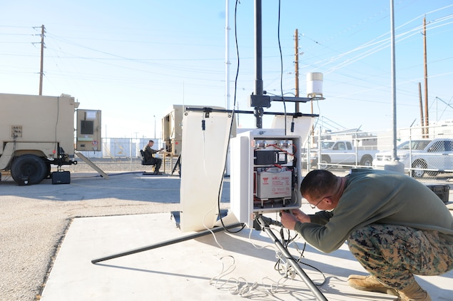 Sgt. Dustin Jones, left, station forecaster, checks information coming in from the remote transmitter while Lance Cpl. Charles Eichler, station weather equipment maintainer, tightens the wire connections on another remote transmitter at the Marine Corps Air Station in Yuma, Ariz., Nov. 30, 2010. The transmitters are part of the new Meteorological Mobile Facility Next Generation Replacement System which consists of a humvee, trailer, two remote transmitters, one local transmitter, radar and the ability to tap into weather satellites and is due to replace old, static equipment. The system is the first in the Corps and Yuma is being used as a test bed before it is used throughout the Corps.