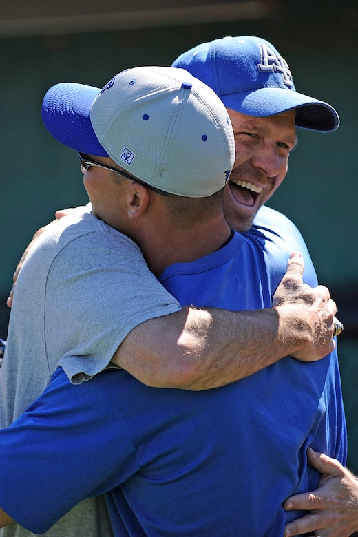 Air Force baseball head coach Michael Kazlausky, facing camera, hugs Troy Simon, an all-american catcher who graduated from the Air Force Academy in 1992, during an Air Force baseball reunion at the Academy Sept. 24, 2010. More than 50 alumni attended the three day reunion Sept. 24-26. (U.S. Air Force photo/Mike Kaplan)