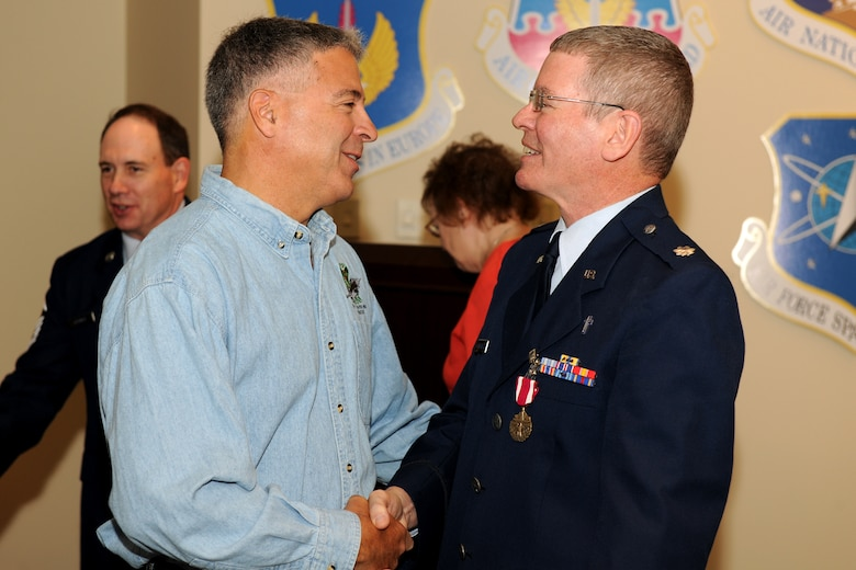 Col. (Ret.) Tony Basile, former Commander of the 174th Fighter Wing, congratulates Lt. Col. Decker on his retirement from the Air National Guard during his retirement on the 1st of October 2010. Lt. Col. Decker served more than 24 years in the Air Force and Air National Guard and had been assigned as the 174th FW Chaplain for the past 10 years. (US Air Force Photo by: SSgt James N. Faso II/Released)