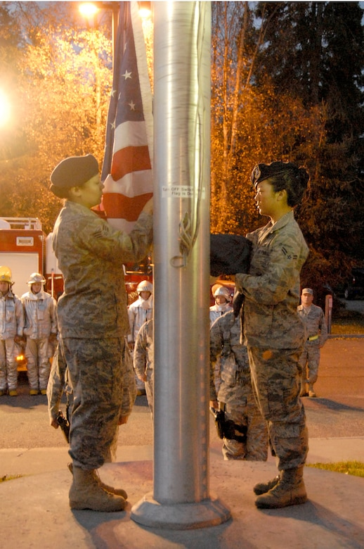 KULIS AIR NATIONAL GUARD BASE, Alaska -- Senior Airman Laurel Foster (left) and Airman 1st Class Alice Chun, both members of the 176th Security Forces Squadron, prepare to raise the U.S. flag as part of an Oct. 3, 2010 ceremony here marking National Fallen Firefighters Memorial Weekend. Fire departments around the country annually observe the ceremony, organized by the National Fallen Firefighters Foundation and the Department of Homeland Security's U.S. Fire Administration. Alaska Air National Guard photo by Master Sgt. Shannon Oleson.